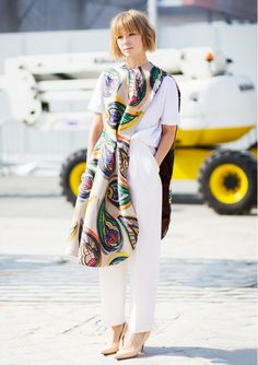 An all white shirt and pant ensemble is worn with a boldly patterned layer piece.