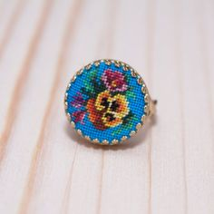 Jewelry: Ring with pansies on blue. Miniature embroidery petit point. Exclusive jewelry. The blue round ring. Needlecraft.