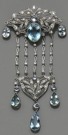 An aquamarine, diamond and platinum brooch, circa 1930's  the wide kite-shape top of filigree design, centering a bezel-set round and oval-shaped aquamarines, the foliate motif set with European and single-cut diamonds, suspending on either side an oval-shaped aquamarine, and five diamond-set navette-shaped link chains terminating with a triangular-shaped openwork plaque, set with single-cut diamonds, completed by three pendants of bezel-set round and pear-shaped aquamarines