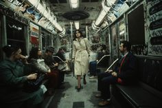 U.S. A woman walks through a heavily graffitied subway car, NYC, 1981 // Christopher Morris