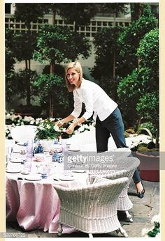Princess Marie-Chantal of Greece arranging daisies in a vase on a low table; the princess is wearing dark slacks and a white blouse, she is looking to the left and smiling