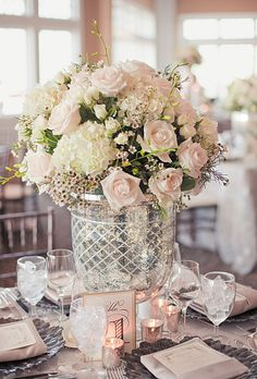 Brides.com: . The reception was held in the ballroom, where tables displayed tall and low arrangements of roses, ranunculuses, and hydrangeas in mercury glass vases and silver vessels. All flowers were by Bloom Floral Design Studio.Alyssa and Kevin worked with wedding planner Danielle Vogelheim of N|M Event Design.