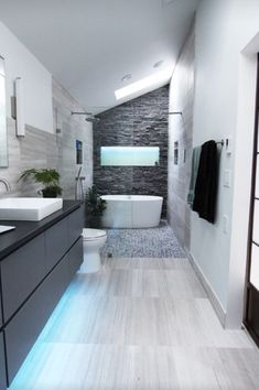 Love the tub and slate tile with doorless glass wall. Space saver.