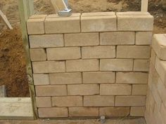 Compressed earth brick walls. The earth brick is manufactured on site or in a central location with local soil and a compressed earth brick machine provided by Earth Home. The bricks are as strong as concrete or fired bricks but are much more environmentally sustainable and lower cost.