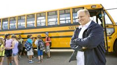 A bus driver greets students outside the bus.
