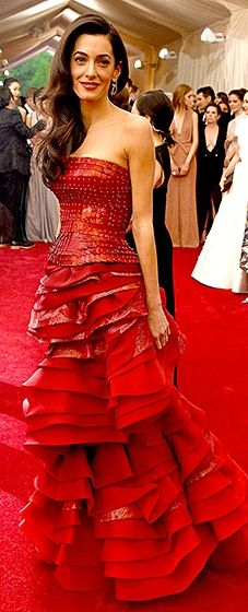 The British barrister was red-hot in a ruffled, multimedia John Galliano dress. She modeled retro curls, pushed over one shoulder, and a crimson statement lip.
