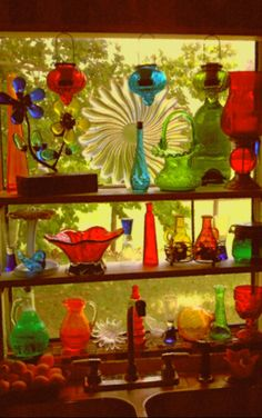 My kitchen window made by adding shelves and adding a collection of colored glass bottles and plates.