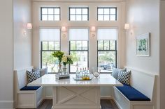 Cottage dining nook is filled with built-in benches lined with cobalt blue cushions facing each ...
