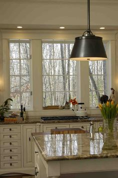 Stove in front of a window,love the window,the light and the kitchen..so pretty