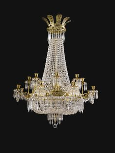 A Regency style cut-glass chandelier with sixteen lights, of tent and waterfall design,  the top corona ornamented with pierced foliate designs supporting strands of cut glass drops, the lower corona supporting the branches with dolphin and anthemion motifs  3ft. 11¾in., 2ft. 11½in.