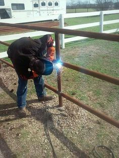 Welding pipe fencing around the ranch.