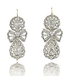 A PAIR OF FINE GEORGE III DIAMOND EAR PENDANTS Each composed of an old-cut diamond cluster top with scrolling openwork diamond surround, to a similarly-set bow design spacer panel and old-cut pear shaped diamond cluster drop of matching design, closed-set in silver, circa 1770, 6.3cm long