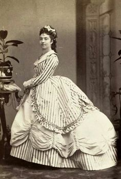 She looks very proud of her in-style dress. Late 1860s which is a totally transition between the full elliptical hoop and the puffy bustle of the early 1870s. Nice stripes too!