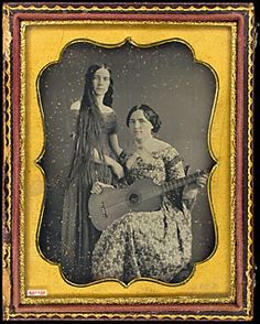 Two women, one standing, very long hair, shallow neckline dress. Woman seated, holding guitar, wearing brooch. 1/4 plate dag