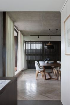 the ceiling light and chair. Large scale herringbone parquetry floor. Exposed concrete ceiling.