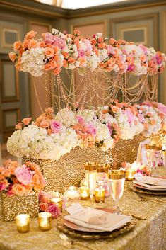 Tablescape of white, pink, and apricot flowers and warm elements of gold and candlelight.