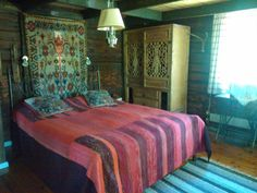 """Our cottage double bed, bedcover """"poppana"""" loomed by my mother. Finnish """"ryijy"""" wall hanging from 1895. Cupboard made of old Chinese window shutters and reclaimed wood. Rag rug loomed by my mother. Old oil lamp electrified."""