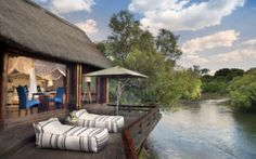 Chundu's two regal lodges lie on a private stretch of the mighty Zambezi River, just upstream from Victoria Falls in Zambia. Chutes Victoria, Spa Lounge, Jordan Travel, River Lodge, Safari Adventure, Outdoor Swimming Pool, Brutalist, Lodges, Vacation Spots