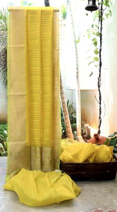 YELLOW IRIDESCENT GREEN SOUTH KORA SILK HAS COMPLIMENTING GOLD BORDER AND PALLU. THE GREEN SELVEDGE GIVES IT A FINISHING LOOK.