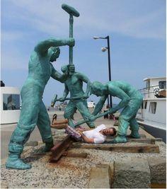 Un homme fait mine de se faire frapper par des statues