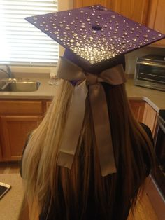 Ombré jeweled graduation cap with silver bow on back.