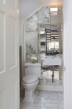 In a small bathroom, introducing a mirror will instantly create interest and space. This room has simple, clean decor and the beautiful tarnished mirror takes all the focus, reflecting and refracting the scene behind in its distressed hue. Image: houzz.com, courtesy of TY Larkins Interiors