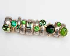 Julia Beusch. Selection of rings in sterling silver, 18 carat yellow gold, tourmaline, emerald, tsavorite.
