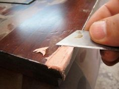 Use a razor blade to score the area so that the filler has some roughness to adhere to. On the damaged section, make several small cuts in the wood in a crisscross pattern.