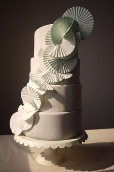 Intertwined mint green fans wrap around this four-tiered cake for a contemporary twist.