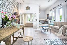 Aranżacja otwartej przestrzeni w stylu skandynawskim z drewnianym, solidnym stołem