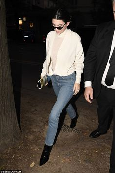 Model behavior: Kendall covered up in a pair of tight blue button fly jeans as she sported a large creamy cardigan on top