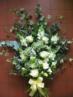 A flat bouquet or spray work well as the main piece on the casket. This one is in classic white and greens.
