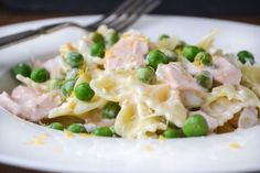 This Farfalle with Salmon, Lemon, and Peas is a delicious pasta recipe with chunks of tender salmon, and garden peas in a to-die-for creamy lemon sauce! This quick weeknight dinner is an old family favorite, I'm not sure why I've never posted it here before.  The dinner comes together in the time it takes the pasta to cook, and the flavor is wonderfully lemony.   I love salmon, and this is one way to make a half a pound stretch to feed four.  The ingredient list is short: farfalle (or bow…
