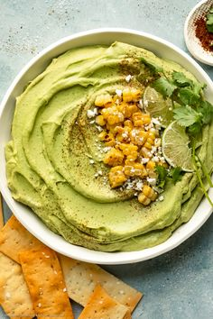 Overhead photo of Spicy Avocado Hummus topped with charred corn, crumbled cheese, lime wedges and fresh cilantro in a large white serving bowl with pita strips and a ramekin of sriracha powder next to the bowl. Chickpea Hummus, Avocado Hummus, Black Bean Hummus, Healthy Snacks, Healthy Eating, Hummus Recipe, Lime Wedge, Cilantro, Spicy
