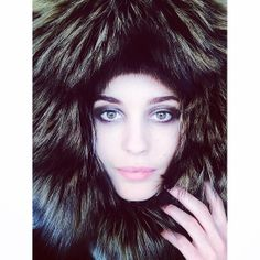 The Danish model wears an oversized fur hood that brings out her green eyes.