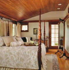 Warm wood planks enhance this bedroom's vaulted ceiling, a matching line of crown molding continues beneath the peaked gable. Love all the trim and the paned glass door!