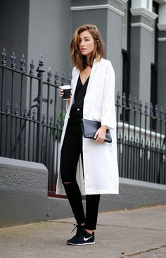 Leather clutch, knee cut jeans, white coat, plain v-neck shirt, sneakers