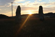 Standing stones aligned betwixt the setting sun.