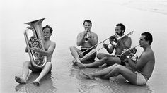 Musicians from the London Symphony Orchestra playing their instruments on Daytona Beach, Florida, 1967