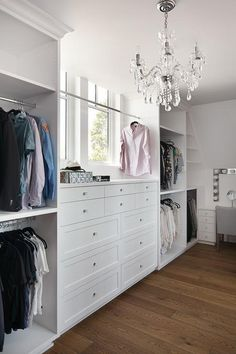 Flanked by stacked clothing rails, this walk in closet is equipped with a white built-in dresser accented with glass knobs and positioned beneath a tension rod clothing rail mounted in front of a window lit by a crystal chandelier.