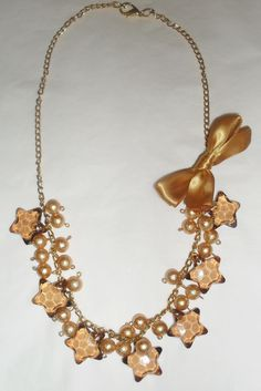 Divertido collar dorado con estrellas sepia y detalle de moño satinado