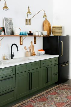 Last week we posted our studio kitchenette reveal and everyone had so many questions about our DIY black fridge with the brass pulls! When we started planning out our studio kitchen design we fell i Kitchenette Studio, Petite Kitchenette, Basement Kitchenette, Farmhouse Kitchen Decor, Diy Kitchen, Kitchen Ideas, Kitchen Storage, Olive Green Kitchen, 1950s Kitchen