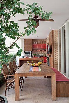 A intenção da designer de interiores Marina Linhares era deixar este espaço com cara de área externa, daí a escolha de cimento queimado e madeira. Pintados de vermelho, os armários guardam utensílios para churrasco