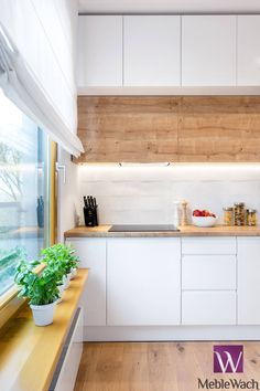 This kitchen balances modern and natural elements perfectly with the little herb pots and the use of wood. We love it. REALIZACJA WARSZAWA WILANÓW : Lighting by MEBLE WACH