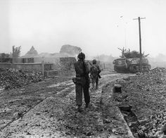 Americans walking through the ruins of Naha Okinawa Japan May 1945.