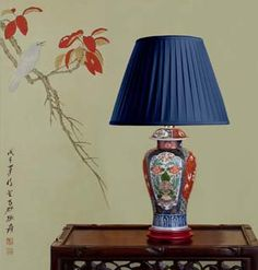 "19th century, Japanese Imari, baluster shaped antique lamp.     The lamp decorated in a bright Imari palette of  underglaze cobalt blue, iron red and green, the decoration finely gilded.  The lamp with its original domed cover  decorated as per the lamp base.  The lamp seated on a custom made maple wood stand, lacquered in red.  Meiji Era-Circa 1870  Overall height (including shade) 22""/56 cm    (Note: Shade not included with this lamp base   but may be ordered separately)"