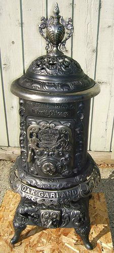 """Oak Garland No 18A wood burning parlor stove made by the Michigan Stove Co.( Detroit & Chicago), Circa 1890. Measures 5' tall with 22"""" square base stand. Diameter of the fire pot is 18"""". This beauty has a nice large 10""""W. X 14"""" H. feed door. Will easily take 18"""" logs and burn for hours of warmth. The dome swings out to expose a cook top with 7 1/4"""" and 3"""" stove plates. Stove is located 15 miles east of Madison, Wisconsin."""