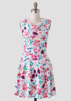 This striking white dress features a saturated floral print in hues of pink, fuchsia, green, mint, and yellow.