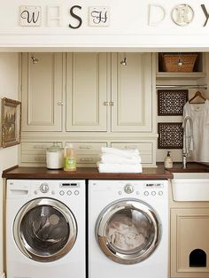 Smart use of space in a small laundry room: countertop over washer & dryer for folding clothes, full length cabinets and hanging rack above, and litter box under sink.