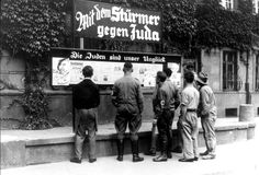 "Germany, Germans reading the antisemetic weekly newspaper Der Stuermer posted in the street. Above the display case is written ""With 'Der Stuermer' against the Jews"" and over the newspaper ""The Jews are our misfortune."""